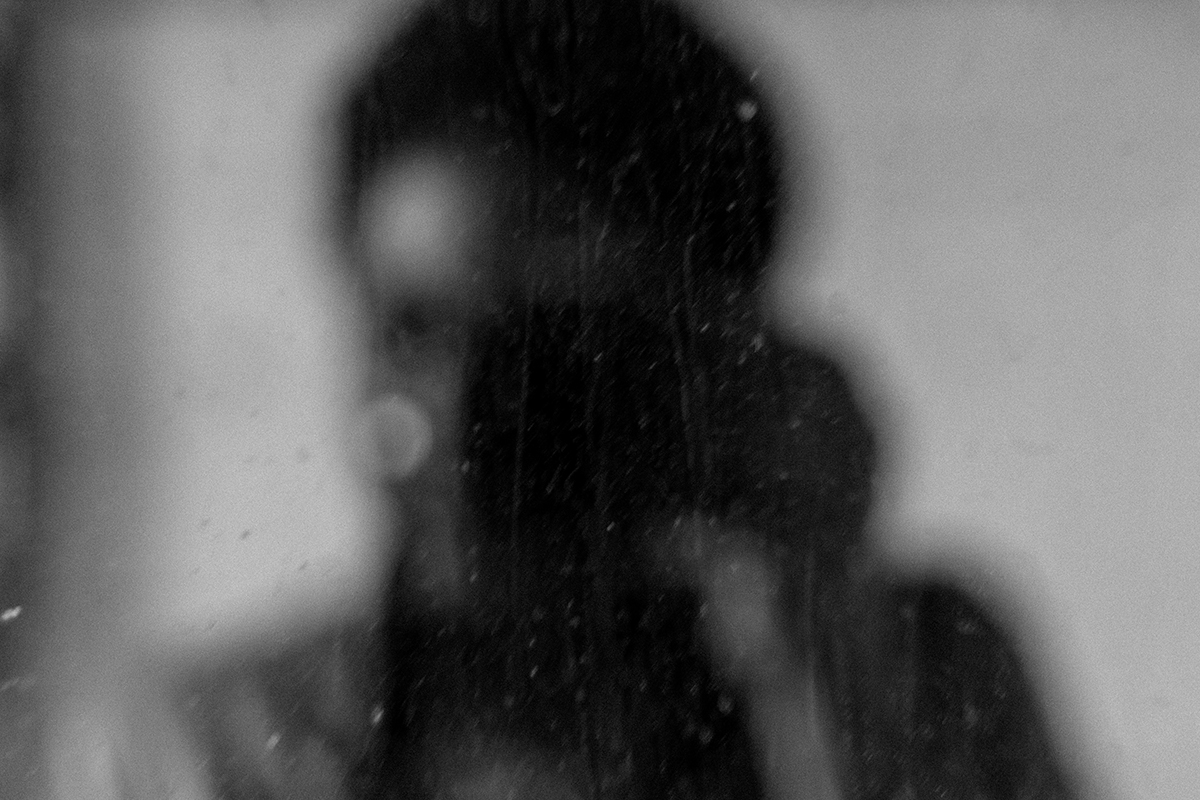 blurred image of a girl holding a camera.
