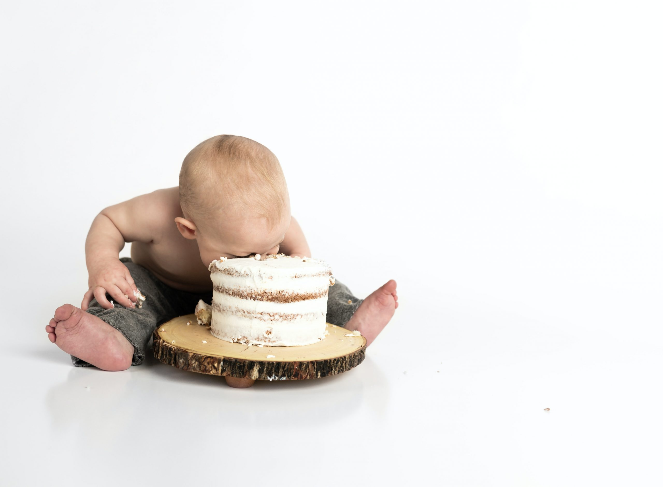 """What's in it for me?"" a baby has his face in cake"
