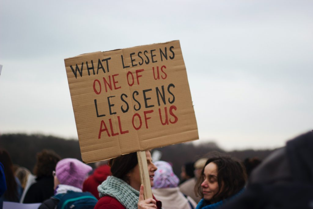 "a sign saying ""what lessens one of us lessens all of us"""